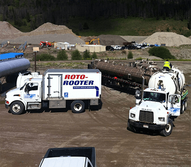 Roto-Rooter Trucks and Vehicles in the Yard.